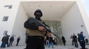 أحد عناصر الأمن التونسيين أمام متحف باردو في 19 آذار/مارس 2015