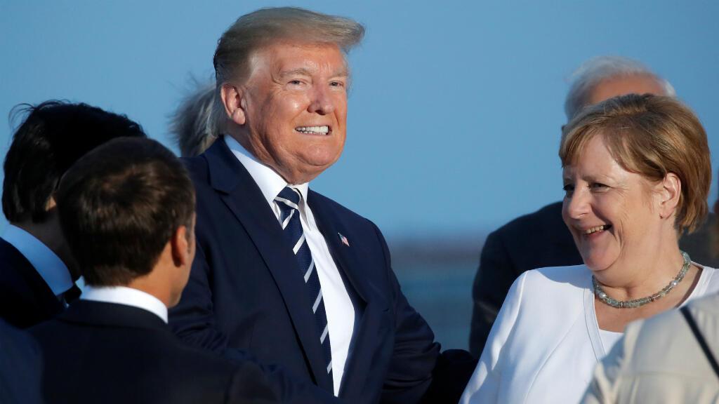 El presidente francés, Emmanuel Macron, reacciona cuando el presidente de los Estados Unidos, Donald Trump, y la canciller alemana, Angela Merkel, se dan la mano durante la cumbre del G7 en Biarritz, Francia, el 25 de agosto de 2019.