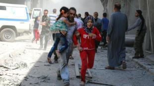 Une famille en fuite après un raid du régime sur l'un des quartiers est de la ville d'Alep, tenu par les rebelles, le 29 avril.
