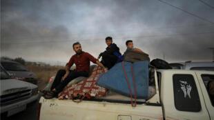 Residentes locales y sus pertenencias en la parte trasera de un camión mientras huyen de la ciudad de Ras al Ain, Siria, 9 de octubre de 2019.