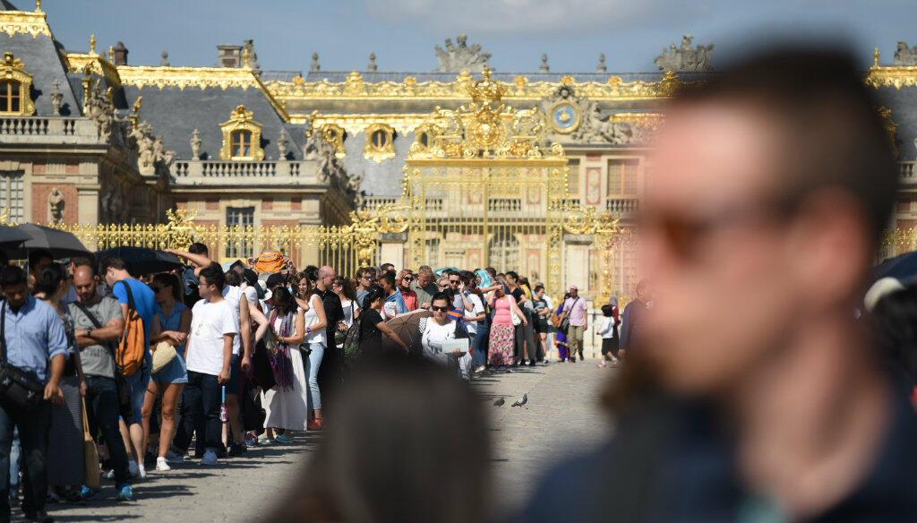 Tourists queue outside the Chateau de Versailles on August 19, 2015.