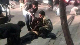 People attempt to help an injured man outside the Lycée Esteqlal in Kabul following a suicide bomb attack