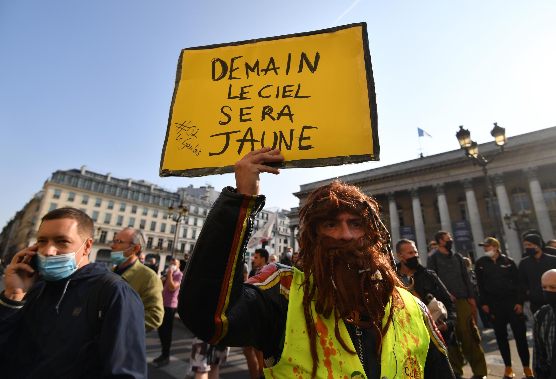 """رجل يحمل لافتة كتب عليها """"غدا ستكون السماء صفراء"""" خلال تجمع جديد لحركة """"السترات الصفراء"""" في باريس 12 سبتمبر/أيلول 2020 ."""