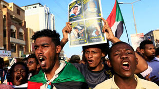 متظاهرون سودانيون يحملون شعارات خلال تجمع حاشد يدعو إلى حل الحزب الحاكم السابق ومحاكمة المسؤولين السابقين في الخرطوم، السودان، 21 أكتوبر/ تشرين الأول  2019.