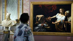 """Une femme devant le tableau du peintre italien Le Caravage """"Judith décapitant Holopherne"""" à Rome, le 30 septembre 2009"""