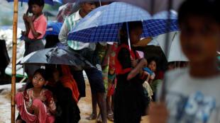 Refugiados rohingyas hacen cola bajo la lluvia a la espera de recibir comida, en un campo cerca de la base de Cox's Bazar. 10/20/2017