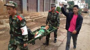 Des secouristes chinois transportent un enfant blessé, dimanche 3 août