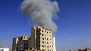 Un bâtiment dont se dégage une épaisse fumée grise à Sanaa après les frappes aériennes du 16 mai.