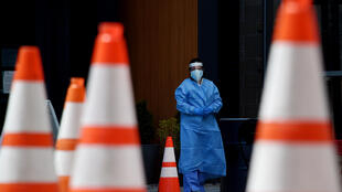 Healthcare workers wait for patients to be tested at a walk-in Covid-19 testing site in Arlington, Virginia