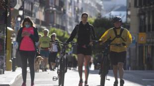 Des personnes marchent ou font du sport dans une rue de Madrid pendant les heures autorisées, le 10 mai 2020 en Espagne