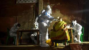 Un trabajador sanitario recoge una muestra de un residente de una zona contaminada de Calcuta para realizar una prueba de COVID-19 el 23 de julio de 2020