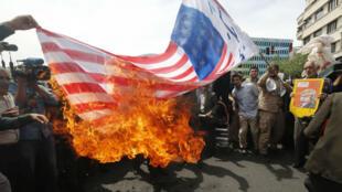 Des manifestants ont brûlé des drapeaux américains, vendredi 11 mai 2018, à Téhéran.