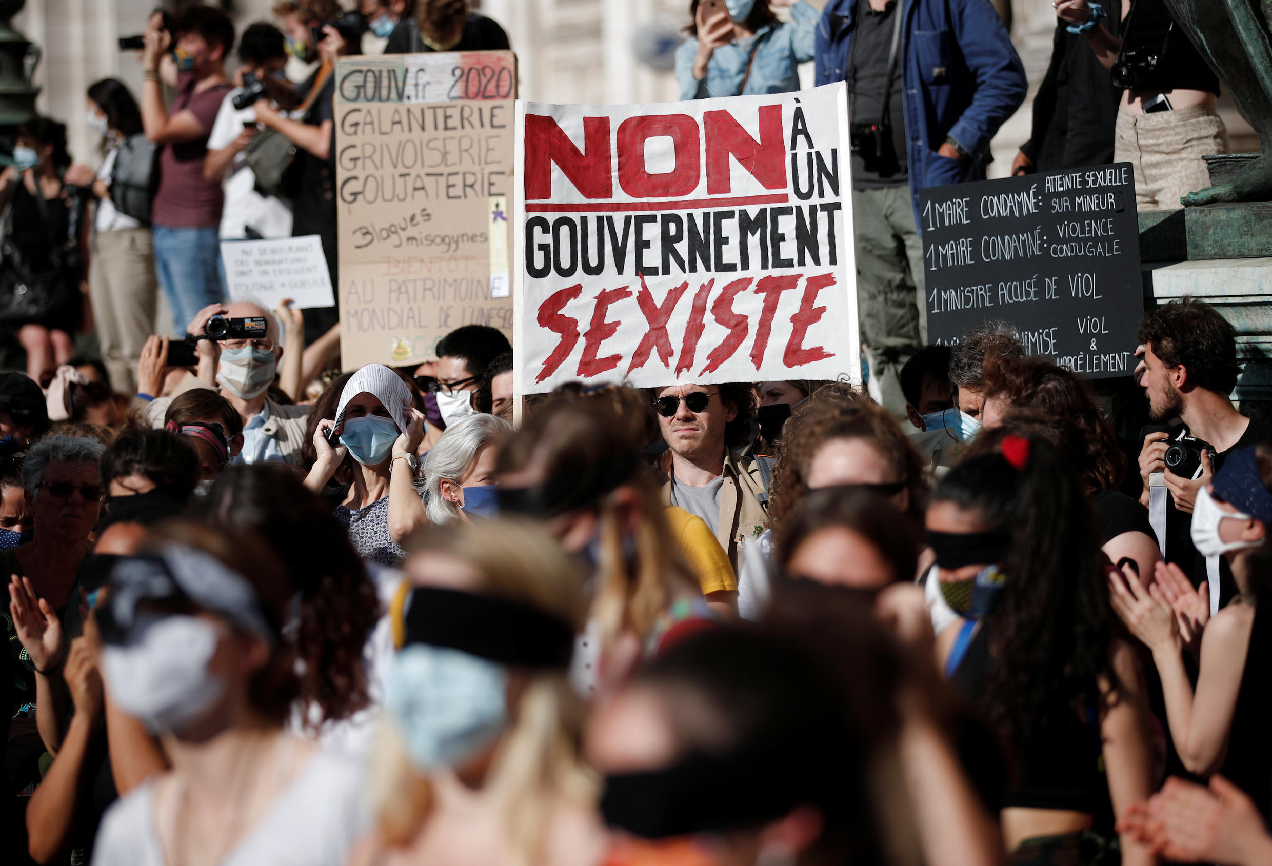 """A placard reading """"No to a sexist government"""" is seen at a rally outside Paris city hall on July 10, one of several protests against the appointment of Interior Minister Gérald Darmanin."""