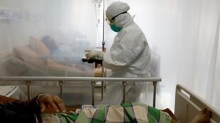 ممرضة تقدم وجبات الطعام لمرضى مصابين بفيروس كورونا في أحد مستشفيات مدينة باغور بإندونيسيا، 26 كانون الثاني/يناير 2020.