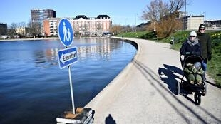 Un panneau indique aux passants le sens de la promenade autour de ce lac de Copenhague, pour limiter les risques de contagion du Covid-19, le 21 mars 2020.
