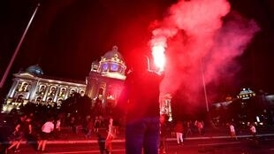A protestor holds a flare as Serbian police fires tear gas in front of the National Assembly building in Belgrade, on July 7, 2020, to disperse thousands of protesters angry at the return of a weekend coronavirus curfew