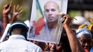 Une militante brandit un portrait de Karim Wade lors d'un meeting de l'opposition, le 4 février 2015 à Dakar.