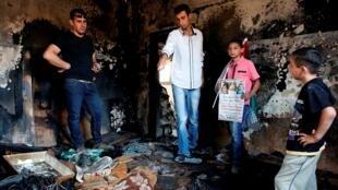 Des Palestiniens constatent les dégâts causés par un incendie criminel qui a provoqué en juillet 2015 la mort de trois membres d'une famille palestinienne.