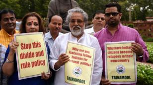 Des membres du Parlement brandissant des pancartes contre un projet accusé de viser la minorité musulmane.