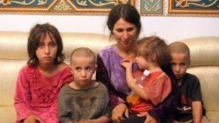 """صورة وزعتها وكالة الأنباء السورية (سانا) في 20 تشرين الأول/أكتوبر 2018 لأمرأة وأطفالها الأربعة من بين ستة أشخاص أفرج عنهم من 27 درزياً خطفهم تنظيم """"الدولة الإسلامية"""" خلال تبادل للمحتجزين، لدى وصولهم إلى مبنى حكومي في السويداء"""