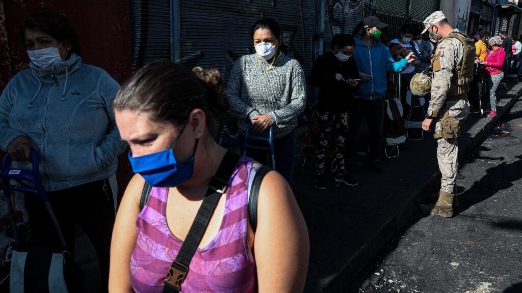 """Un soldado verifica la identidad de un comprador en la fila para ingresar al mercado """"La Vega"""" en Santiago, Chile, el viernes 15 de mayo de 2020, en medio de restricciones para frenar la propagación del nuevo coronavirus."""