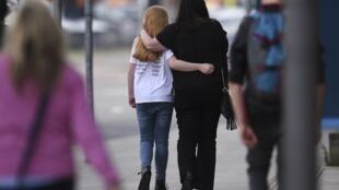طفلة مع والدتها تغادران نزلا غداة الانفجار في مانشستر شمال بريطانيا 23 مايو 2017