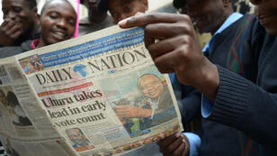 Un groupe d'hommes lit un journal au lendemain du scrutin présidentiel au Kenya.