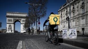 Un livreur à vélo sur les Champs-Élysées, le 23 mars 2020, à Paris.