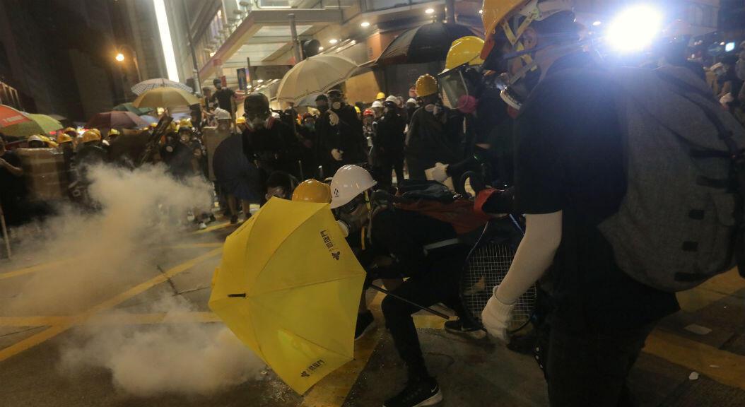 Grupos de manifestantes tratan de huir de los gases lacrimógenos disparados por la policía, durante una manifestación el 28 de julio de 2019. Miles de manifestantes desafiaron a las autoridades a realizar una marcha no autorizada a través de Hong Kong, un día después de
