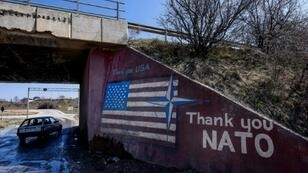 """A car drives past graffiti reading """"Thank You NATO"""" and featuring the US flag near the village of Stagovo, Kosovo on March 24, 2019, 20 years after the start of the alliance's bombing campaign"""