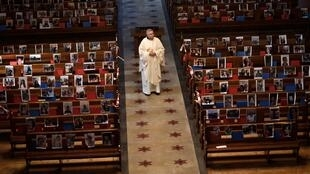 Switzerland has reopened its places of worship one week early, further easing coronavirus restrictions. Here a priest is surrounded by pictures of his parishoners who could not attend services at his church in Neuchatel earlier this month