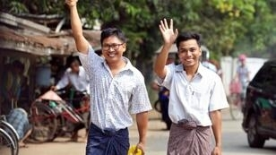 Journalists Wa Lone and Kyaw Soe Oo gesture as they walk out of Insein prison gate after being freed in a presidential amnesty in Yangon on May 7, 2019