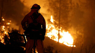 """Un bombero observa cómo las llamas avanzan cuesta arriba hacia las casas mientras las cuadrillas luchan contra el incendio denominado """"Carr Fire"""", al oeste de Redding, California, EE. UU., el 27 de julio de 2018."""