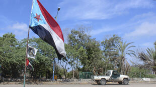 Fighters with Yemen's Southern Transitional Council drive past a separatist flag -- the flag of the former nation of South Yemen -- in the city of Aden