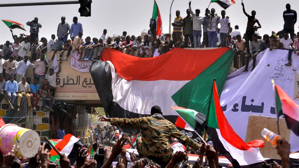 La multitud corea consignas y llevan sus banderas nacionales, luego de que el ministro de Defensa de Sudán, Awad Mohamed Ahmed Ibn Auf, dijo que el presidente Omar al-Bashir había sido detenido, en Jartum, Sudán, el 11 de abril de 2019.