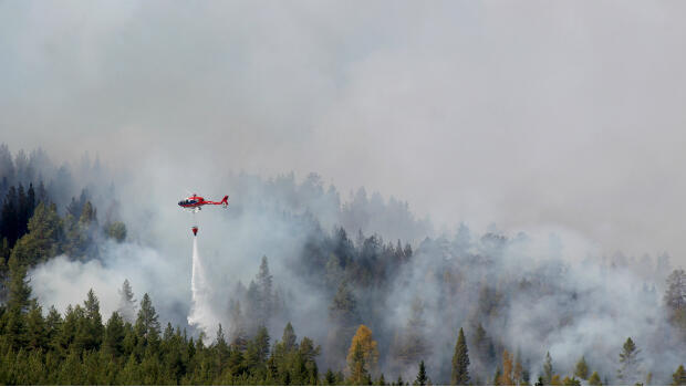 Firefighters use helicopters to fight wildfires outside Hammarstrand in Sweden, on July 16, 2018.