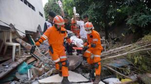 Des secouristes évacuant des survivants à Palu, le 30 septembre.