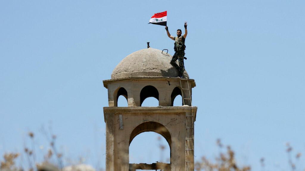 Un soldado de las fuerzas del Ejército sirio ondea la bandera del país en un sector de la ciudad de Al Quneitra, el 27 de julio de 2018.