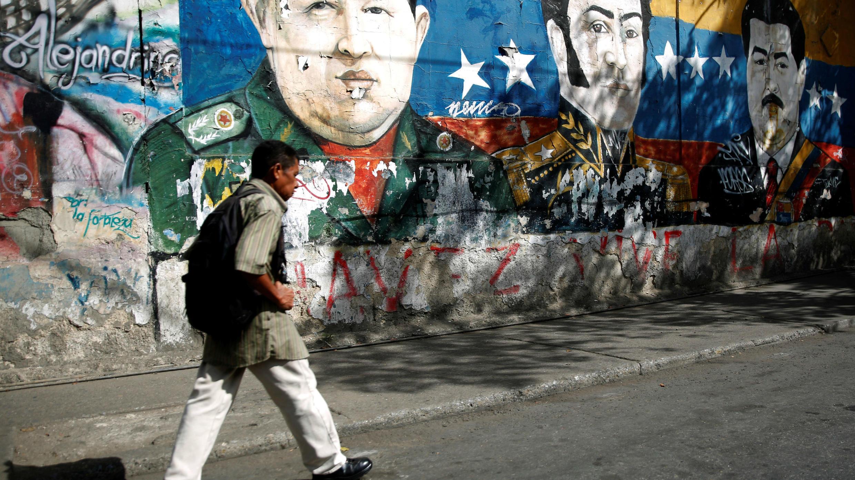 Un hombre camina frente a los graffitis del héroe revolucionario sudamericano Simón Bolívar, el fallecido Hugo Chávez y el presidente Nicolás Maduro en el barrio José Félix Ribas en Caracas, Venezuela, el 30 de enero de 2019.