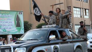 Image fournie par un média jihadiste montrant des hommes de l'EI dans la ville de Raqqa, en juin 2014