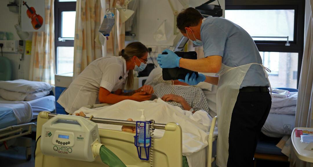 Un cura y una estudiante de enfermería ayudan a un paciente con Covid-19 a comunicarse con su familia, que no lo puede visitar debido a las restricciones de confinamiento, desde el hospital donde se encuentra en Blackburn, Reino Unido, el 14 de mayo de 2020.