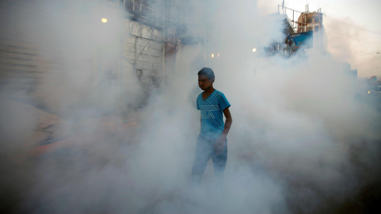 Se ve a un niño entre el humo mientras los trabajadores de salud pública rocían insecticida en medio de temores de un nuevo brote de cólera en Sanaa, Yemen, el 7 de junio de 2018.