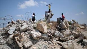 """Des enfants jouent dans les ruines d'un immeuble détruit pendant l'opération militaire israélienne """"Bordure protectrice"""" contre la bande de Gaza, durant l'été 2014."""