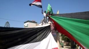 فلسطينيون فرحون بالإعلان عن اتفاق مصالحة بين حركتي فتح وحماس يحتفلون في شوارع غزة وهم يحملون علمين عملاقين لفلسطين ومصر في 12 من تشرين الأول/أكتوبر 2017