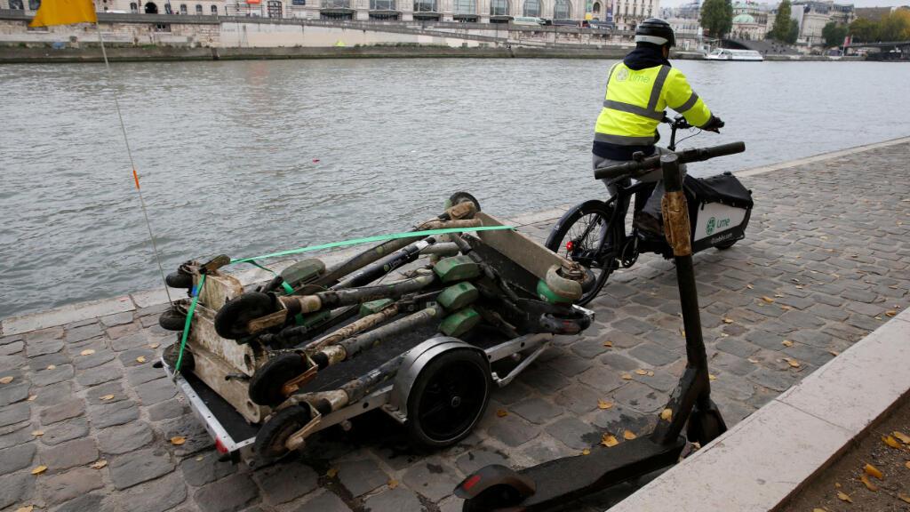 Un empleado de una empresa de patinetes compartidos colecta los scooters eléctricos abandonados en el río Sena en París, el 25 de octubre.