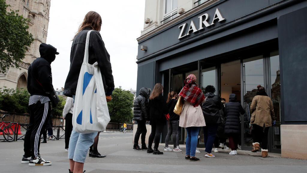Grupos de personas se aglomeran en la entrada del local de ropa Zara en París, durante el primer día de desconfinamiento en Francia, el 11 de mayo de 2020.