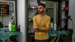 Ahmad Yassine in his Istanbul barbershop where he watched as a crowd attacked his and other Syrian-owned businesses