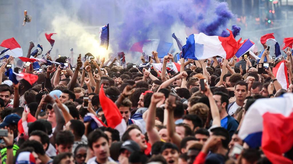 La gente celebra la victoria de Francia en una zona de aficionados en el centro de París el 10 de julio de 2018 tras el silbato final del partido de fútbol de la semifinal de la Copa Mundial Rusia 2018 entre Francia y Bélgica.