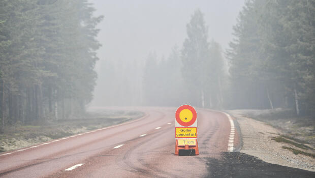 A sign on the road 84 blocked between Ljusdal and Lassekrog because of forest fires is pictured near Ljusdal, Sweden on July 18, 2018.