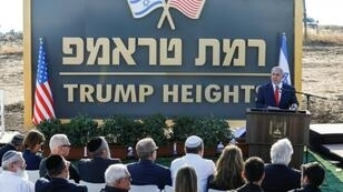 """Israeli Prime Minister Benjamin Netanyahu gives a speech in front of the newly-unveiled sign """"Ramat Trump"""", or """"Trump Heights"""" in English, named after the incumbent US president in the Israeli-annexed Golan Heights on Sunday"""